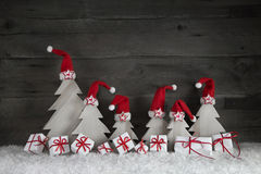Funny christmas trees with santa hats and gift boxes on wooden b Stock Images