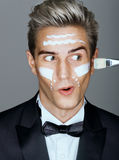 Funny classy man with cream lines on face, spa treatment. Stock Photography