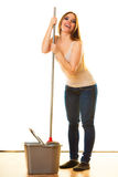 Funny cleaning woman mopping floor. Cleanup housework concept. Funny cleaning girl young woman mopping floor, holding mop white background Royalty Free Stock Photos