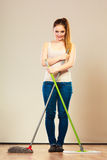 Funny cleaning woman mopping floor. Cleanup housework concept. Funny cleaning lady young woman mopping floor, holding two mops new and old Stock Images