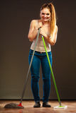 Funny cleaning woman mopping floor. Cleanup housework concept. Funny cleaning lady young woman mopping floor, holding two mops new and old dark background Stock Photos