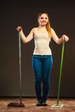 Funny cleaning woman mopping floor. Cleanup housework concept. Funny cleaning lady young woman mopping floor, holding two mops new and old dark background Royalty Free Stock Photography