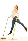 Funny cleaning woman mopping floor jumping. Cleanup housework concept. Funny cleaning lady young woman mopping floor, holding two mops new and old jumping white Stock Photography