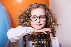 Funny, clever curly teen girl in glasses with wooden abacus on t Stock Photos