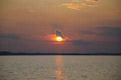 Funny cloud sitting on sun during sunset. The final stage of a cloudy sunset above the huge lake in Karelia region. The picture is colorful and relaxing stock photos