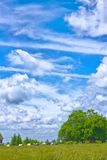 Funny clouds over green meadow Royalty Free Stock Photo