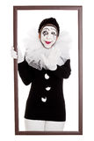 Funny clown in a frame stretches out hand Royalty Free Stock Photos
