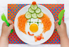 Funny clown fried egg with vegetables for kids royalty free stock photo