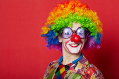 Funny clown with glasses on red. Backround Royalty Free Stock Photo