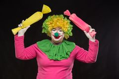 Funny clown with hair and a cheerful make-up holding a gift Royalty Free Stock Photos