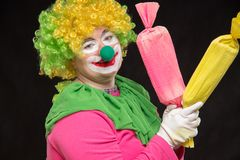 Funny clown with hair and a cheerful make-up holding a gift. Funny clown with shaggy hair and a cheerful make-up holding a gift Royalty Free Stock Images