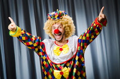 Funny clown in humorous concept. Against curtain stock image