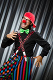 Funny clown in humorous concept. Against curtain stock photo