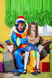 Funny clown with the little girl sit on a sofa. Stock Photo