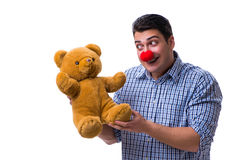 Funny clown man with a soft teddy bear toy isolated on white bac Royalty Free Stock Photo