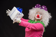 Funny clown with shaggy hair and a cheerful make-up holding a gi Stock Photography