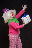 Funny clown with shaggy hair and a cheerful make-up holding a gi Stock Image