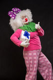 Funny clown with shaggy hair and a cheerful make-up holding a gi Royalty Free Stock Image