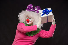 Funny clown with shaggy hair and a cheerful make-up holding a gi Stock Photo
