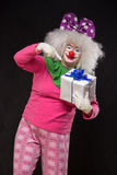 Funny clown with shaggy hair and a cheerful make-up holding a gi Royalty Free Stock Photo