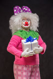 Funny clown with shaggy hair and a cheerful make-up holding a gi Royalty Free Stock Photos