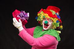 Funny clown with hair and a cheerful make-up holding a gift. Funny clown with shaggy hair and a cheerful make-up holding a gift Stock Image