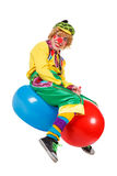 Funny clown sits on balls Royalty Free Stock Image