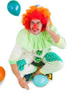 Funny clown sitting on floor Stock Photos