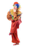 Funny clown standing on one leg. Isolated Royalty Free Stock Photos