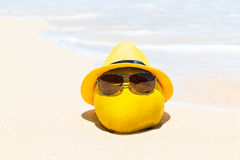 Funny coconut in sunglasses and yellow hat lies on a sandy tropi Stock Photos