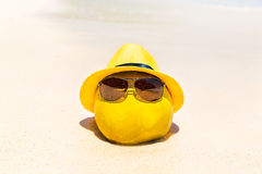 Funny coconut in sunglasses and yellow hat lies on a sandy tropi Royalty Free Stock Images