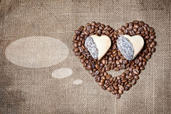 Funny coffee face. Funny face from coffee beans and cookies in shapes of heart on textured sack with dialog cloud. Free space for text Stock Photo