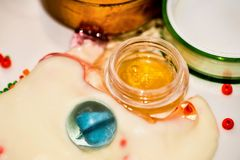 Funny colorful abstract background with cosmetics cream, transparent blue glass ball and golden lotion Stock Photos