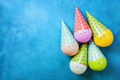 Funny colorful balloons in caps on blue table top view. Creative concept for birthday background. Flat lay. Stock Image