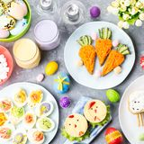 Funny colorful Easter food for kids with decorations on table. Easter dinner concept stock photography