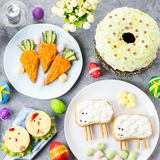 Funny colorful Easter food for kids with decorations on table. Easter dinner concept. Top view stock image