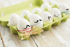 Funny colorful eggs with mustaches in tray stock image