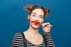 Funny comical young woman making mustache with chilli pepper. Over blue background Royalty Free Stock Image