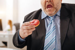 Funny compulsive guy eating a doughnut Royalty Free Stock Images