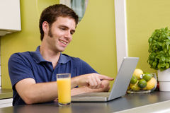 Funny Computer. A young male using a laptop computer in the kicthen, smiling and laughing at what he sees royalty free stock photos