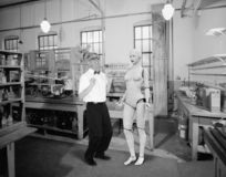 Funny Scientist, Nerd, Robot Love, Sex. A funny computer science technology nerd has built a female robot love sex machine. The scientist is in a vintage retro stock photos