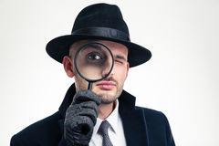 Funny concentrated inspector in black hat looking through the magnifier Royalty Free Stock Image