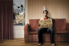 Funny concept of Alien invasion. Man sitting on a couch with an alien outside the window Stock Image