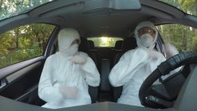 Funny concept of two young hazmat scientists workers in car dancing and driving to contaminated location - stock video footage