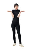 Funny confused clueless young woman in black turtleneck and pants shrugging shoulders Stock Photos