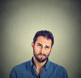 Funny confused skeptical man thinking looking up. Portrait closeup funny confused skeptical man thinking looking up isolated on gray wall background with copy Royalty Free Stock Photo