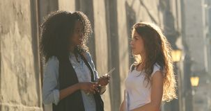 The funny conversating of two charming smiling students in the street. The girl is correcting the hair. The funny conversating of two charming smiling students stock footage