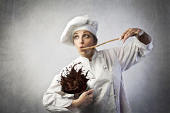 Funny cook. Funny female cook tasting chocolate cream spilling from a pot royalty free stock photo