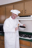 Funny Cook Chef Cooking Bad Tasting Food, Dinner. Funny humor scene of a male chef or short order cook cooking food that doesn't taste good in a kitchen. On his Royalty Free Stock Photo