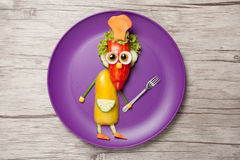 Funny cook with fork made of vegetables on plate. Cook made of pepper, cucumber, carrot, radish, olive corn and salad. He is also holding fork as an atribute of royalty free stock photo